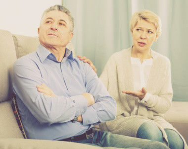 upset mature couple quarreling at home with each other